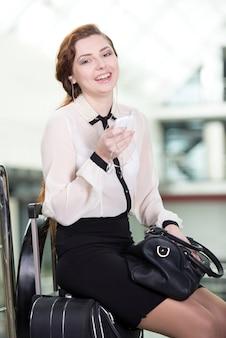 Vrouw met kaartjes op de luchthaven om reizen te reizen.