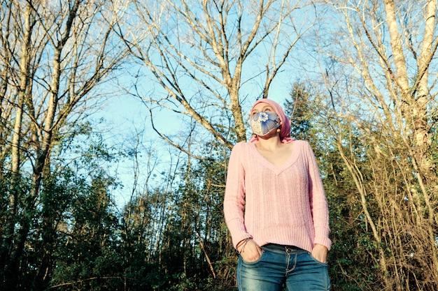 Vrouw met kanker die een roze sjaal en gezichtsmasker draagt terwijl ze geniet van een dag in het wild