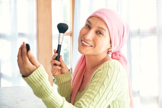 Vrouw met kanker die make-up opdoet en naar de camera kijkt, is zeer hoopvol over haar revalidatie