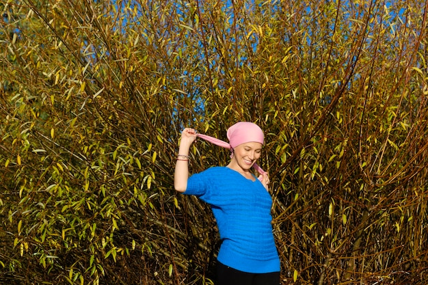 Vrouw met kanker glimlachend en kijken naar de grond in een bos met gele herfstbladeren