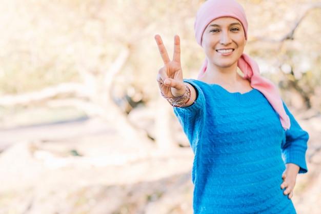 Vrouw met kanker onscherp kijkt naar de camera en glimlacht in een gebaar van overwinning.
