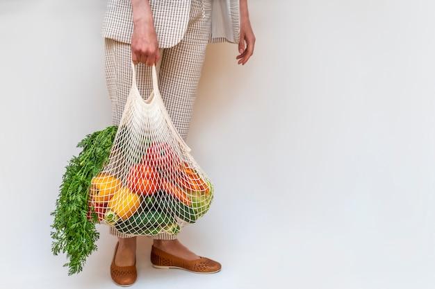 Vrouw met katoenen shopper en herbruikbare mesh boodschappentassen met groenten