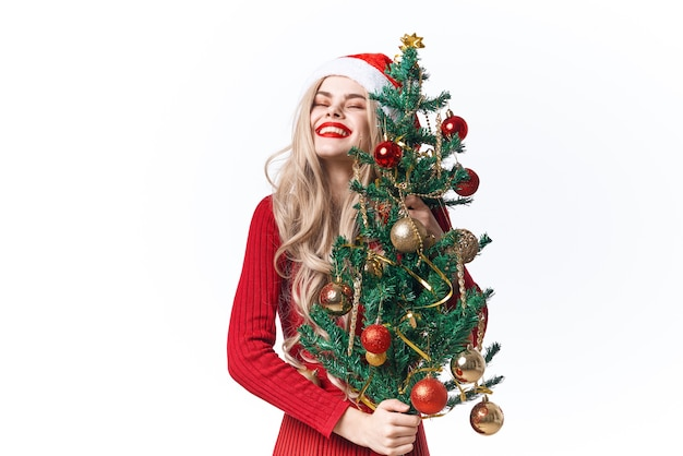 Vrouw met kerstboom in handen speelgoed vakantie kerstversiering