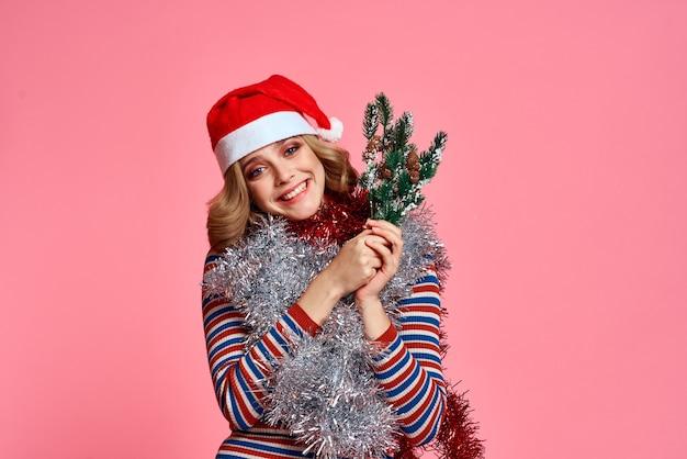 Vrouw met kerstboomtakken in handen rood klatergoud en feestelijke hoed roze achtergrond