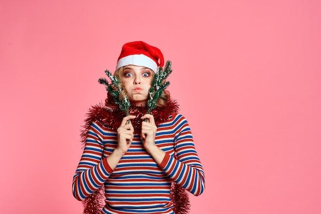 Vrouw met kerstboomtakken in handen rood klatergoud en feestelijke hoed