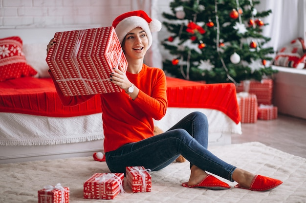 Vrouw met kerstcadeaus door kerstboom