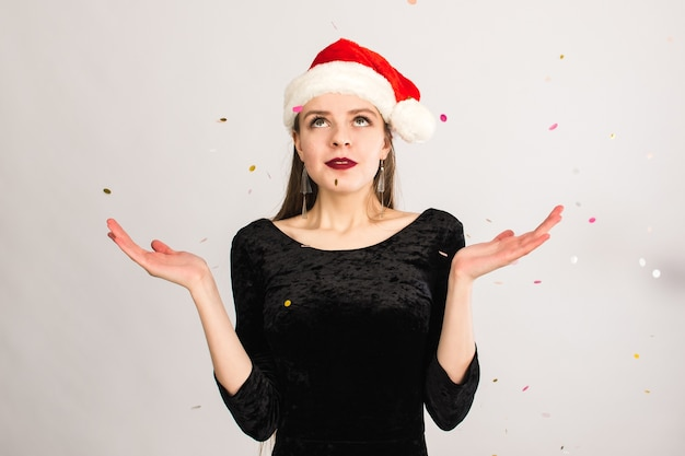Vrouw met kerstmuts confetti gooien