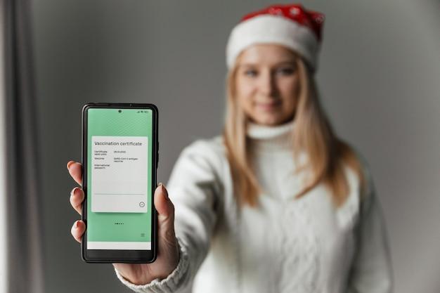 Vrouw met kerstmuts houdt smartphone vast met elektronisch covid-vaccinatiecertificaat