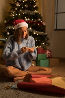 Vrouw met kerstmuts inwikkeling van geschenken