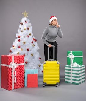 Vrouw met kerstmuts met bagage naast de kerstboom