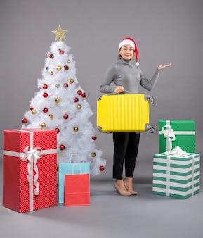 Vrouw met kerstmuts terwijl ze bagage naast de kerstboom houdt