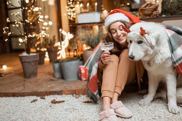 Vrouw met kerstmuts viert met haar schattige hond een nieuwjaarsvakantie, samen zittend op het prachtig versierde terras thuis