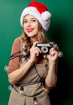 Vrouw met kerstverlichting en vintage camera op groene muur