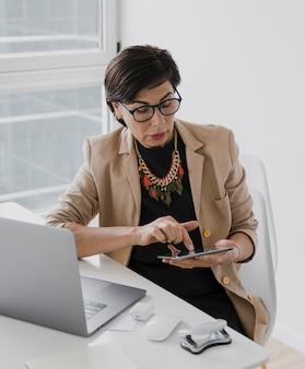 Vrouw met ketting wat betreft een tablet