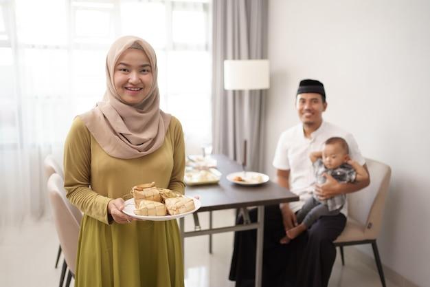 Vrouw met ketupat of rijstwafel voor eid Premium Foto