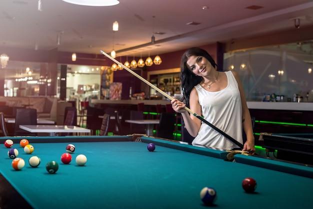 Vrouw met keu poseren in de buurt van biljarttafel in pub