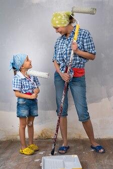 Vrouw met kind meisje dochter huisschilder schildert muur binnenshuis verfroller. repareren doe het zelf thuis