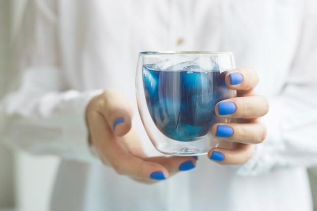 Vrouw met klassieke blauwe manicure houdt een glas matcha blauwe thee