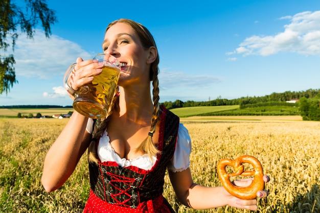Vrouw met klederdracht, bier en krakeling in beieren