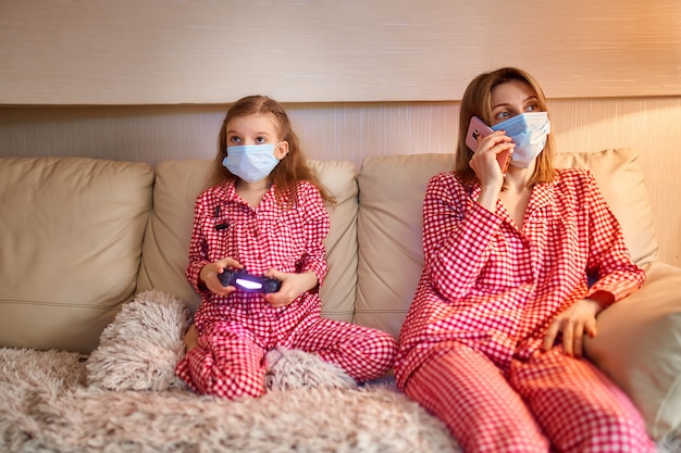 Vrouw met klein kind thuis dragen gezichtsmasker