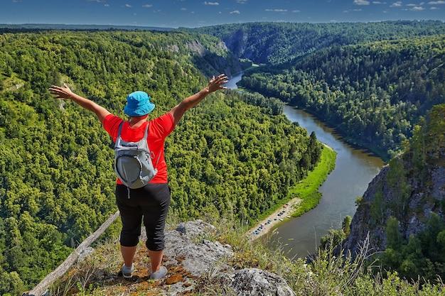 Vrouw met kleine rugzak achter haar veroverde bergtop en geniet ervan haar handen naar boven te steken, ze houdt zich bezig met wandelen en ecotoerisme. b.