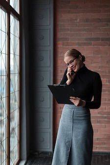 Vrouw met klembord dat over telefoon spreekt
