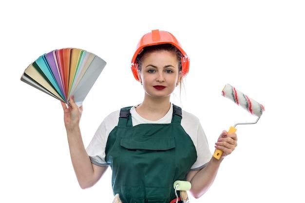 Vrouw met kleurenpalet en verfborstel op witte muur wordt geïsoleerd die
