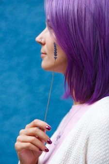 Vrouw met kleurrijk paars haar, draai haar profiel met lavendel in de hand