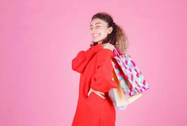 Vrouw met kleurrijke boodschappentassen achter op haar schouder.