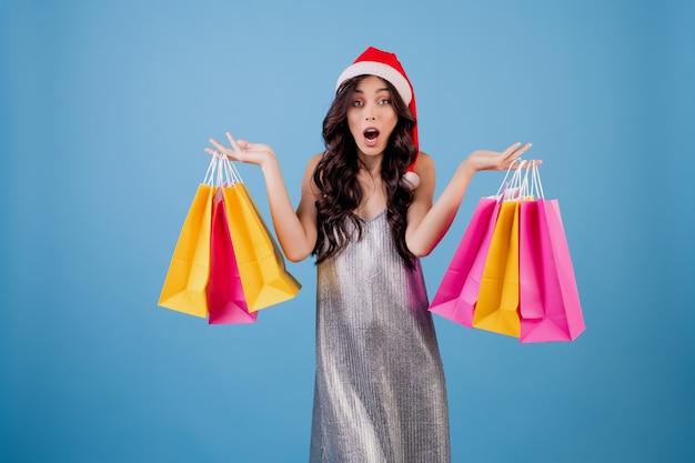 Vrouw met kleurrijke boodschappentassen dragen kerstmuts en -kleding