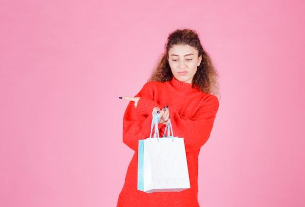 Vrouw met kleurrijke boodschappentassen wijzend aan de linkerkant.