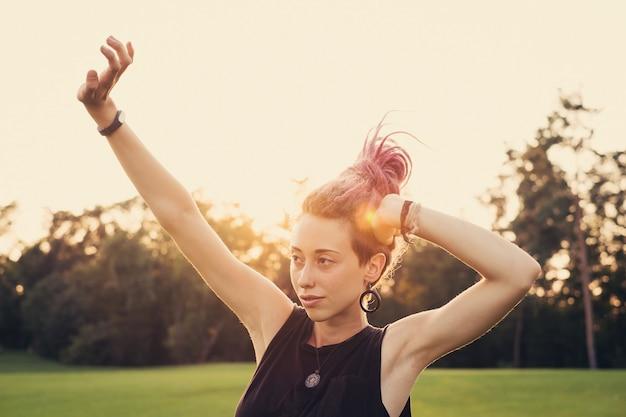 Vrouw met kleurrijke dreadlocks die zich uitstrekken en buiten dansen op zonsondergang vol energie.