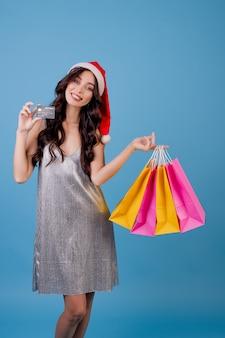 Vrouw met kleurrijke het winkelen zakken en creditcard die kerstmishoed dragen die over blauw wordt geïsoleerd