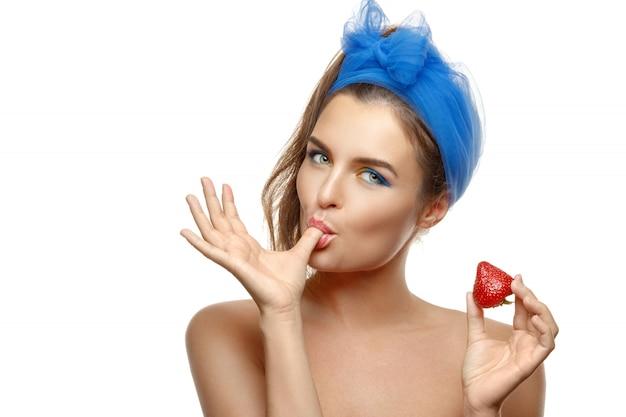 Vrouw met kleurrijke make-up eet aardbei