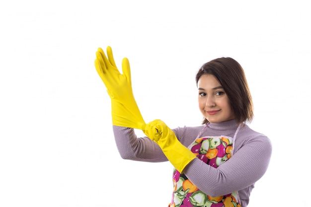 Vrouw met kleurrijke schort die gele handschoenen gebruiken