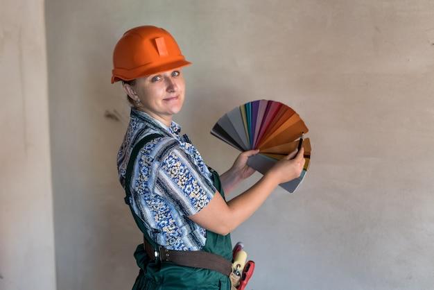 Vrouw met kleurstaal in de buurt van muur in nieuw appartement