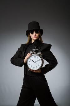 Vrouw met klok in bedrijfsconcept
