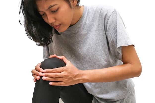 Vrouw met knie met handen met sterke pijn op witte muur