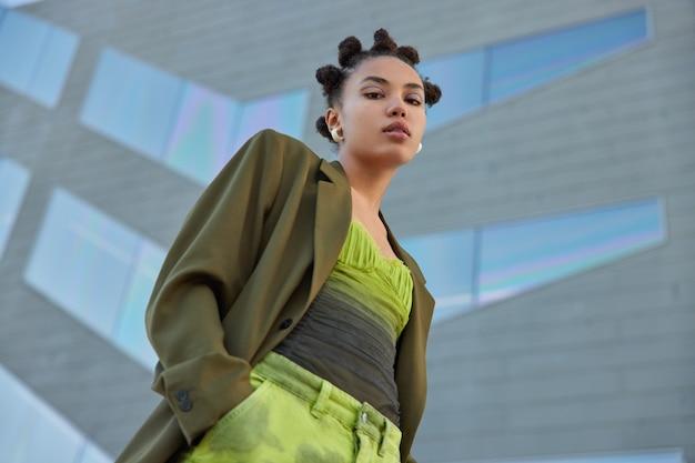 Vrouw met knotkapsel gekleed in modieuze kleding houdt handen in zak kijkt aandachtig naar camera heeft lichte make-up poses tegen grijze muur