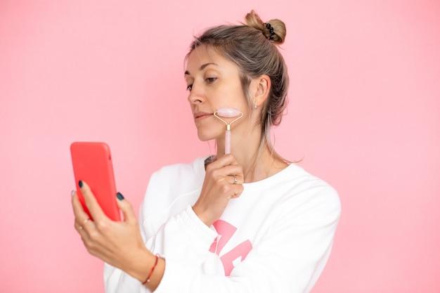 Vrouw met knotkapsel op roze achtergrond geeft een online masterclass over het onderwijzen van massage-guasha in de studio