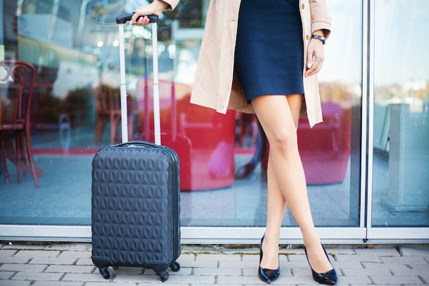 Vrouw met koffer dichtbij luchthavenmuur.