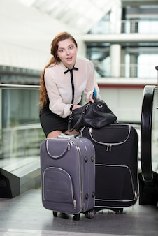 Vrouw met koffer en vliegtuigtickets op de luchthaven.