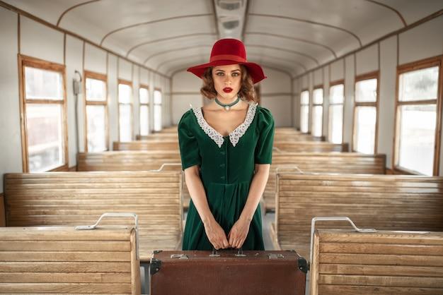 Vrouw met koffer in retro trein, oud wagenbinnenland. spoorwegreis. vintage reis