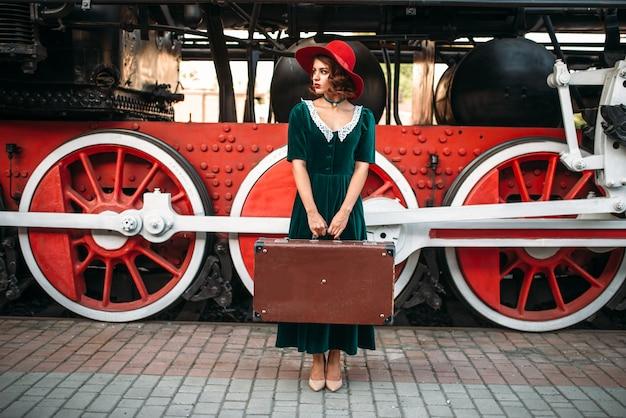 Vrouw met koffer tegen stoomlocomotief