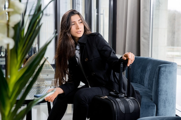Vrouw met koffers die in wachtruimte in de zakenlounge van de luchthaven zitten