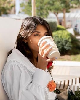 Vrouw met koffie buitenshuis terwijl bloemen
