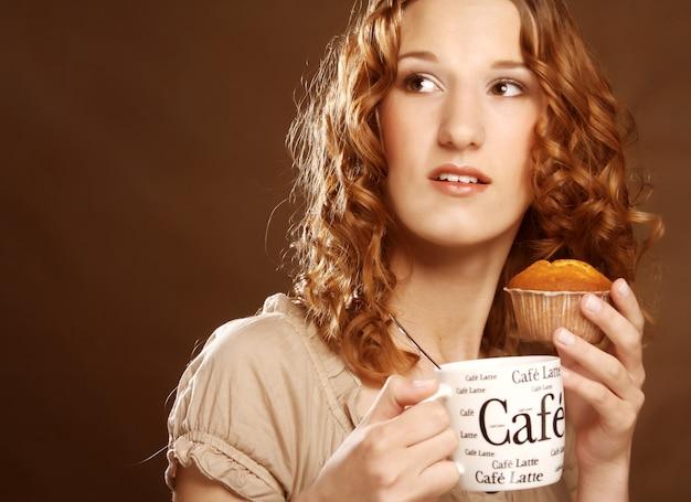 Vrouw met koffie en cake dicht omhooggaand beeld