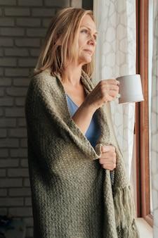 Vrouw met koffie kijkt door het raam tijdens quarantaine