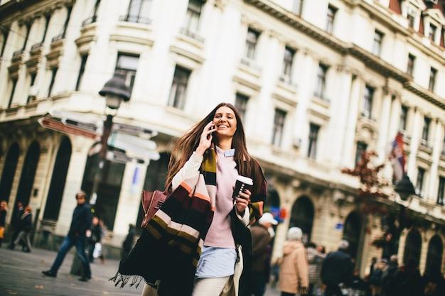 Vrouw met koffie om te gaan en mobiele telefoon in de hand lopend onderaan de straat