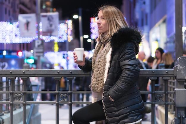 Vrouw met koffie op de straat. mooie modieuze jonge vrouw met koffie in nachtstad.